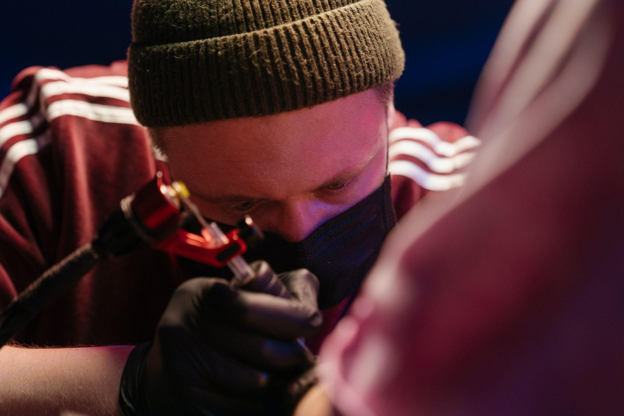 tattoo artist applying a hand tattoo